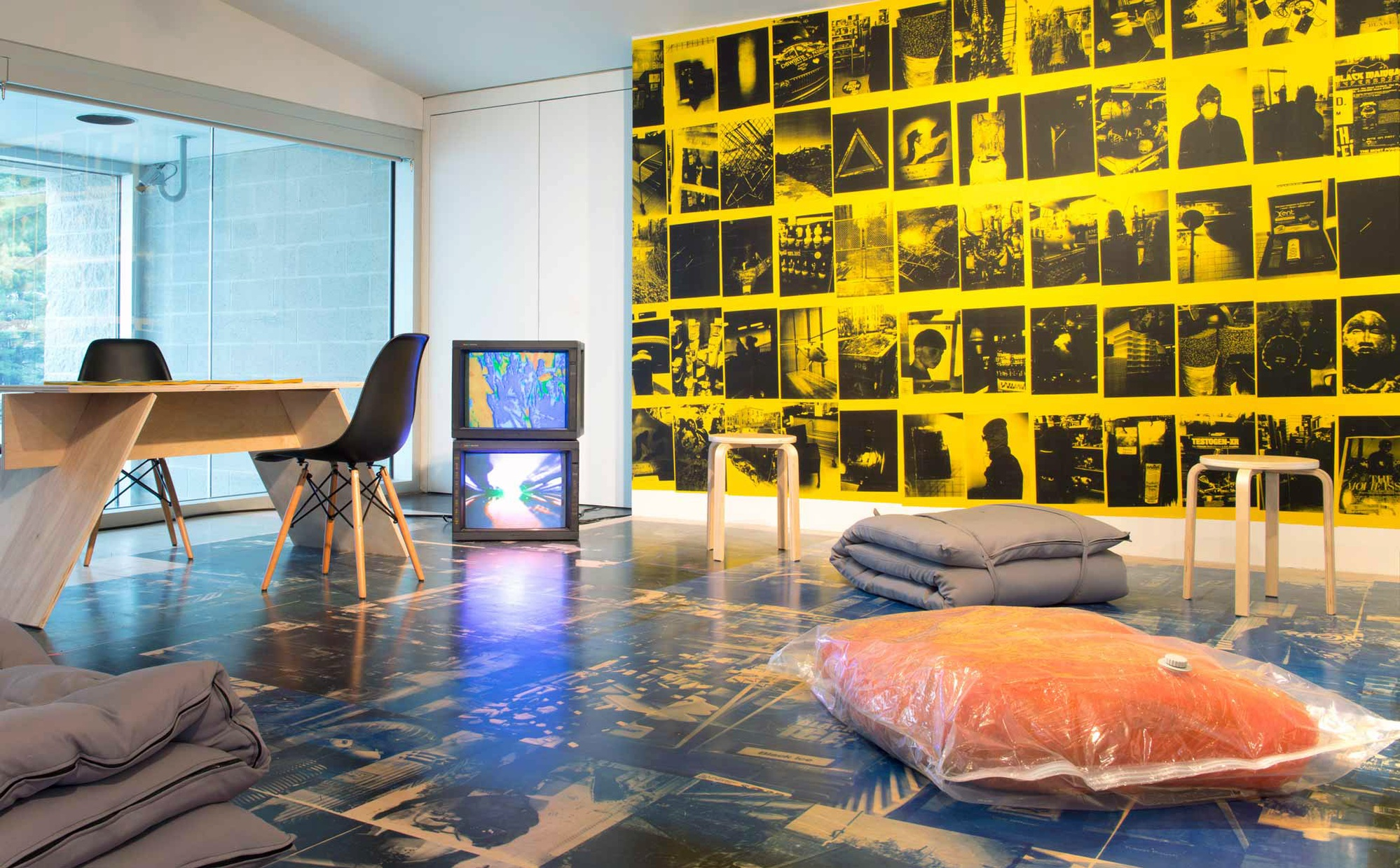 Two TV monitors and various types of seating rest on a wooden floor printed with dark images. Adjacent to the TV monitors, a wall is covered with yellow pamphlets printed with different urban scenes printed in black ink.