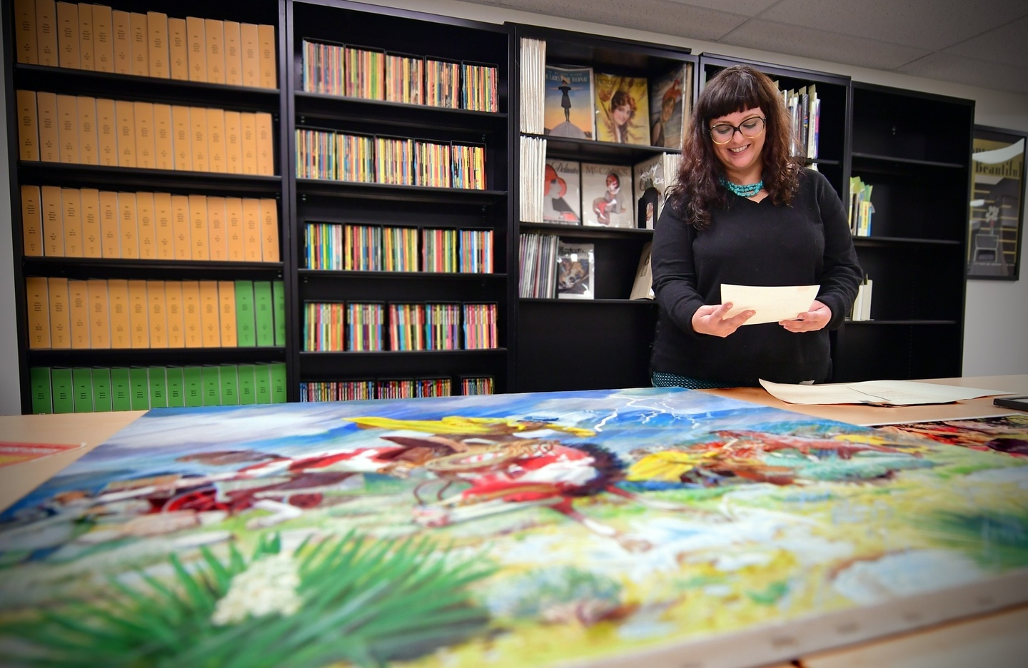 Person looks at original golden age illustrations on a table. Library stacks with periodicals can be seen behind them.