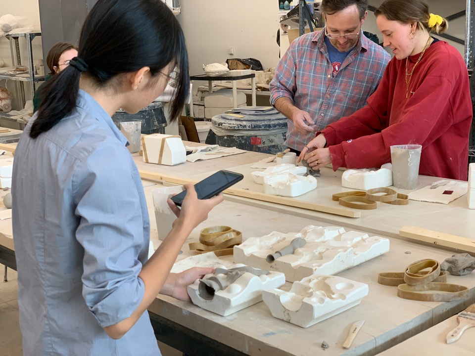 Several students remove slip castings from their molds at a table.