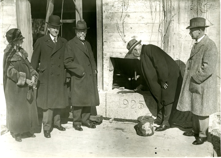 """Black and white photograph of five people in dark coats and hats standing around a cornerstone block with """"1925"""" engraved in it. One person is laying mortar the top."""