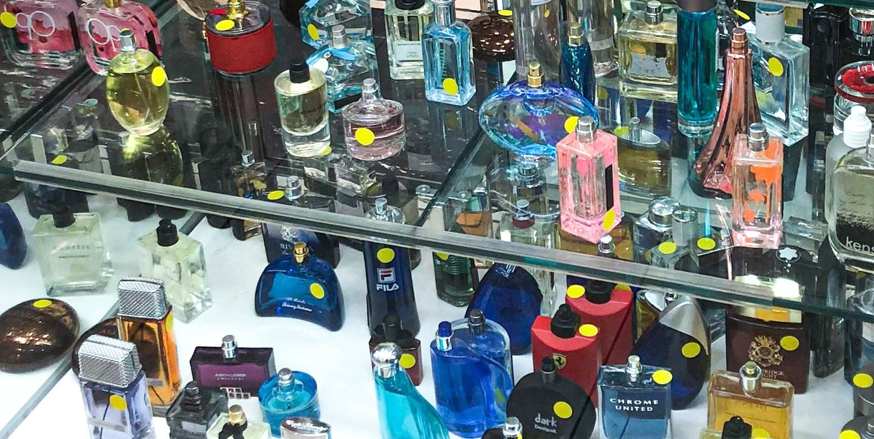 The inside of a store vitrine, dozens of multi-colored glass perfume bottles sit on two shelves. Many bottles have a round bright yellow sticker placed on them.