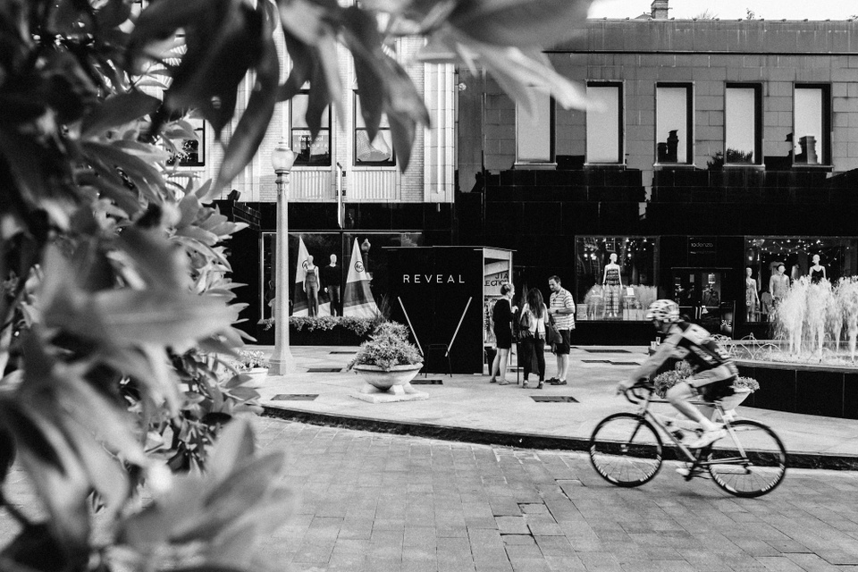 Black-and-white photo of a cobblestone street area in St. Louis' Central West End. A black box pop-up space is visible in the center, next to a water fountain, with the word REVEAL in white lettering.
