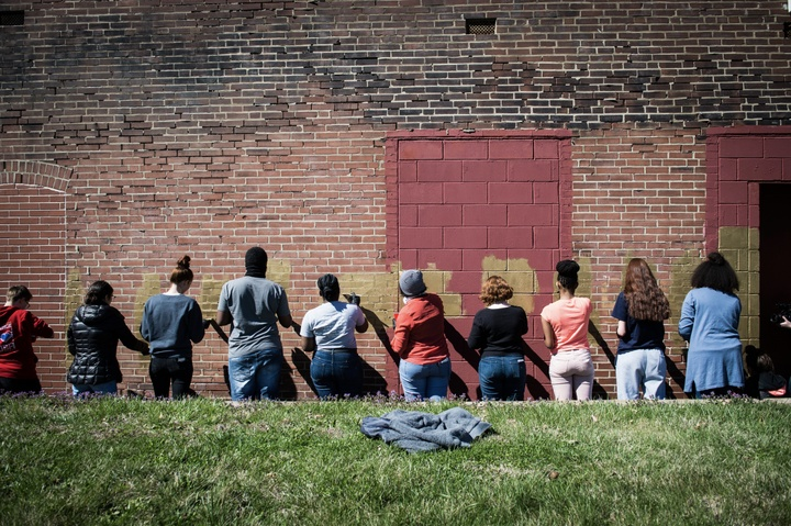 A group of 10 people painting an old, red-brick wall gold.