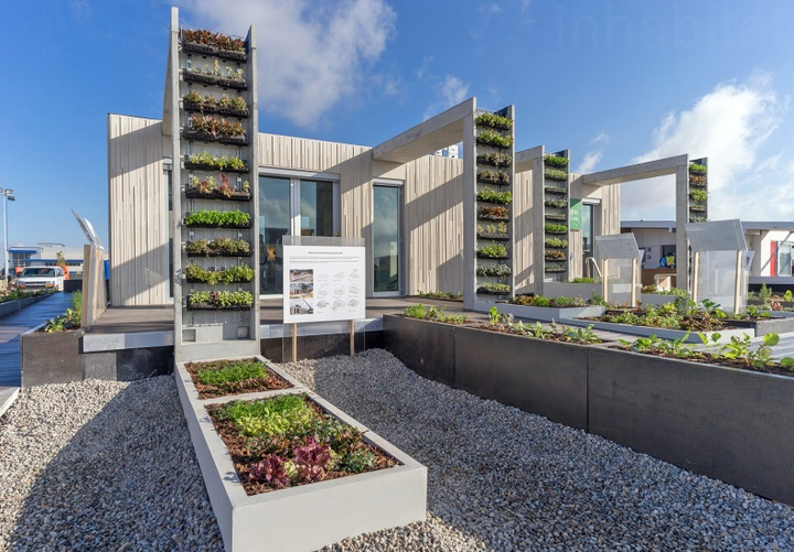 House-sized concrete building with buttress-like extensions that hold vertical gardens.