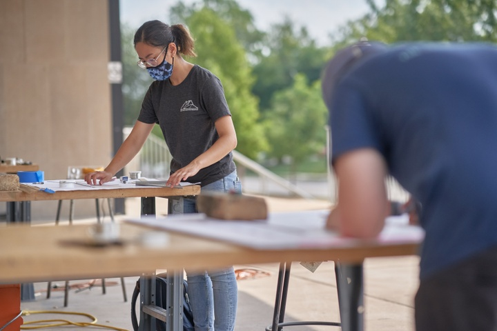 Two people working at worktables on a patio.