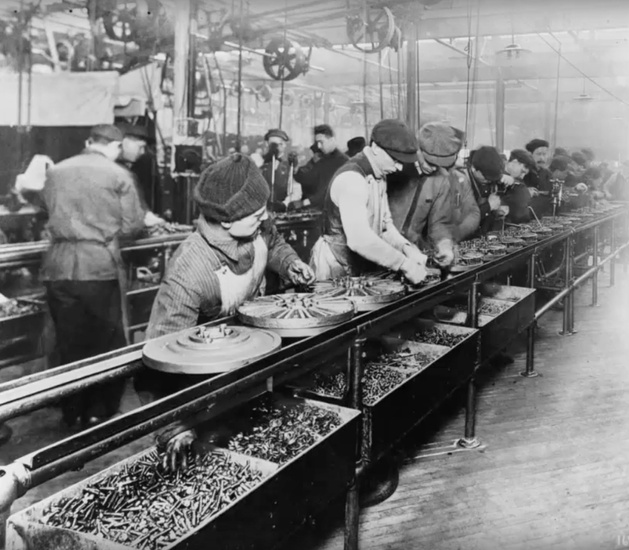 Workers on the first moving assembly line, at the Ford Highland Park Plant, put V-shaped magnets on Model T flywheels to make one-half of the flywheel magneto, 1913.