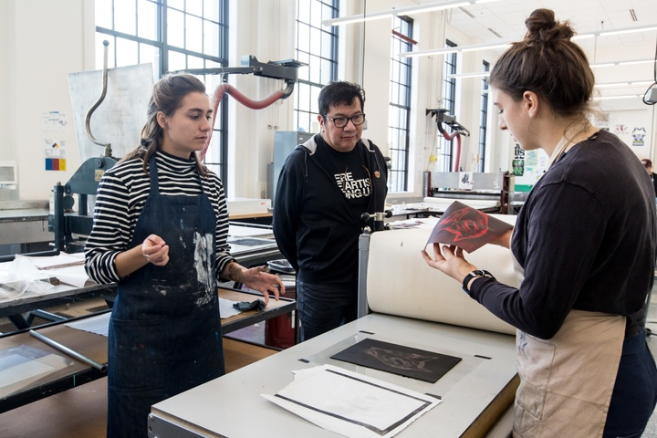 Person checks the quality of a print of a black wolfish head on red paper while two others observe.