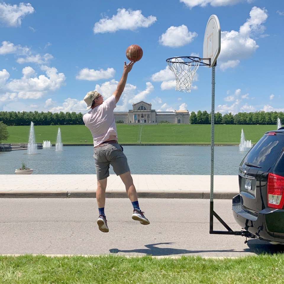 An individual jumping and shooting a basketball, on a temporary court in front of St. Louis Forest Park's Grand Basin