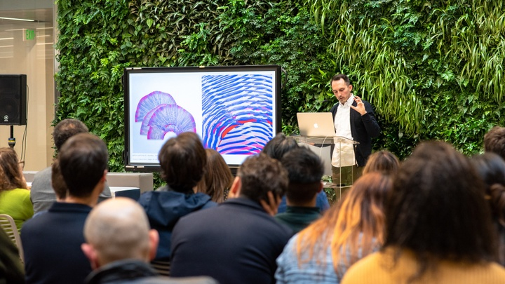 An individual standing in front of a lush green wall of plants delivers a presentation to a seated crowd. A digital monitor featuring architectural work is to his side.