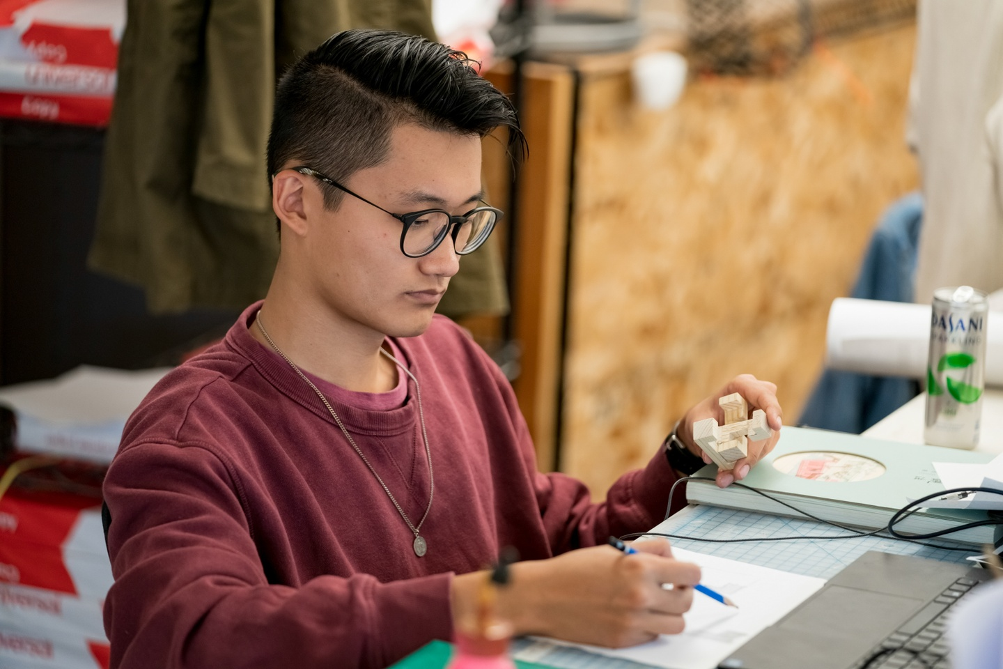 Person sitting at a desk holds a small wooden model in one hand and sketches something with the other.