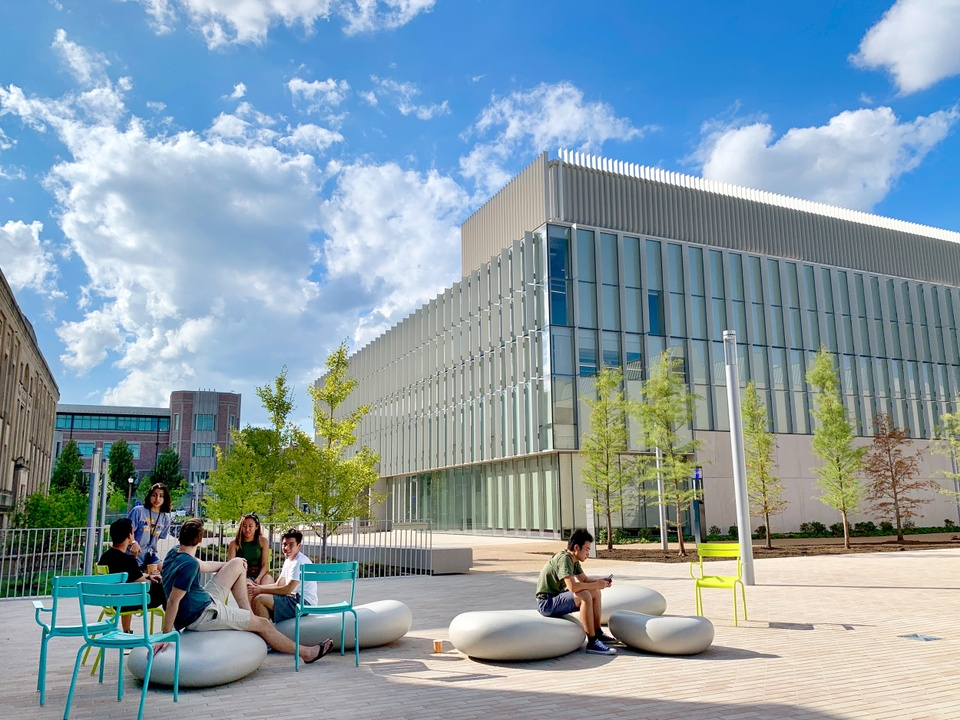 Bricked patio in front of a modern glass walled building. People sit on large smooth concrete boulders and turquoise metal chairs.
