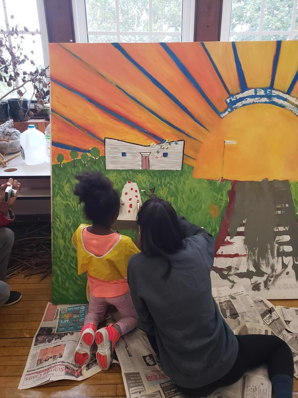 Student paints mural indoors with a child.