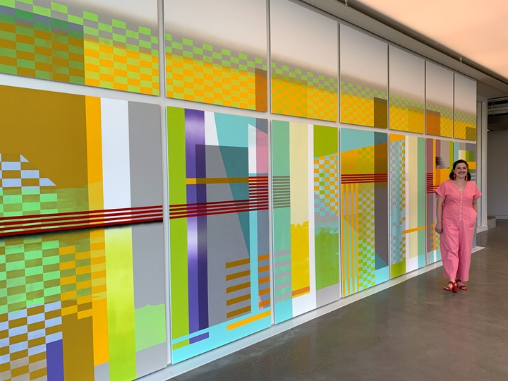 Person poses next to a neon-colored mural made of overlapping geometric shapes and textures.