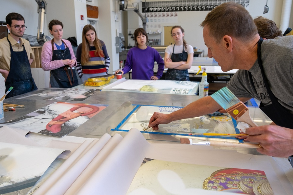 Group of people watch as a person demonstrates drawing on a plexi plate with a crayon.