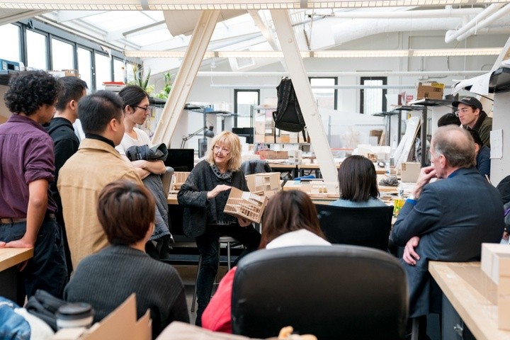 Architect Yvonne Farrell surrounded by a group of students in the architecture studio, discussing an architectural model she is holding.