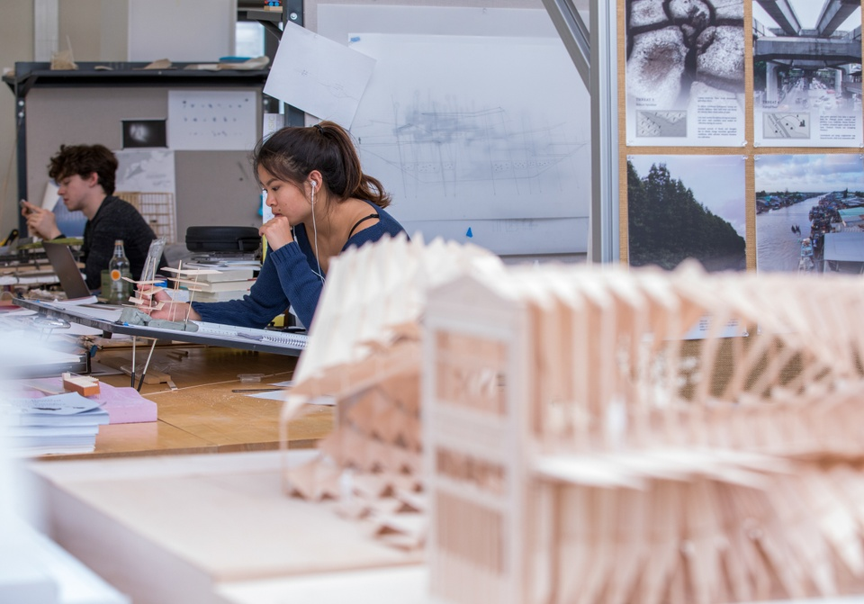 Close-up of basswood model. In the background two people work at spaced out drafting tables.