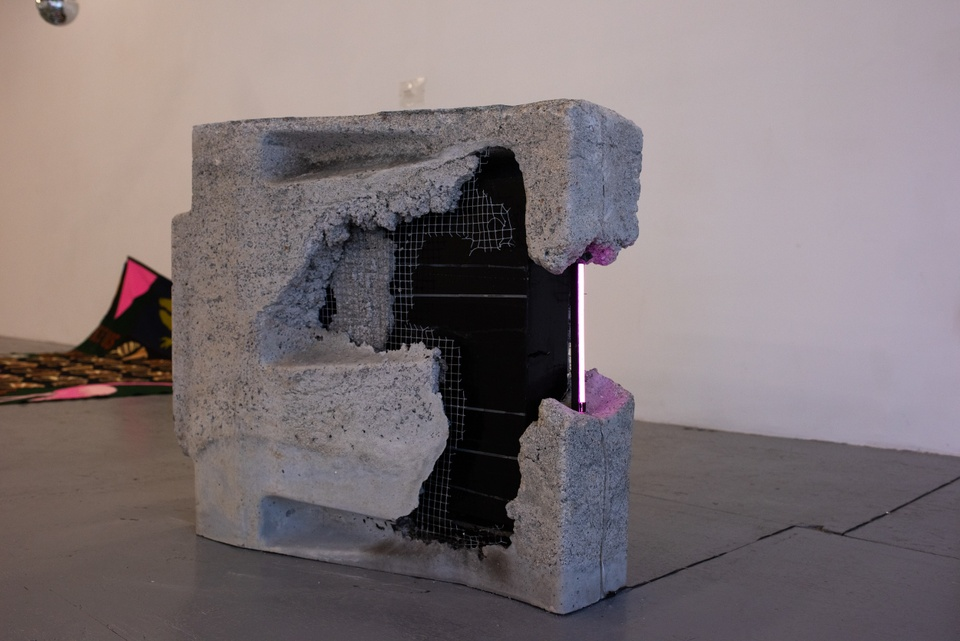 A roughed-up flatscreen tv is half-encased in wire mesh and concrete, sitting on its side on the floor. A neon pink lighting strip runs along the outer edge of the tv screen where it is exposed.