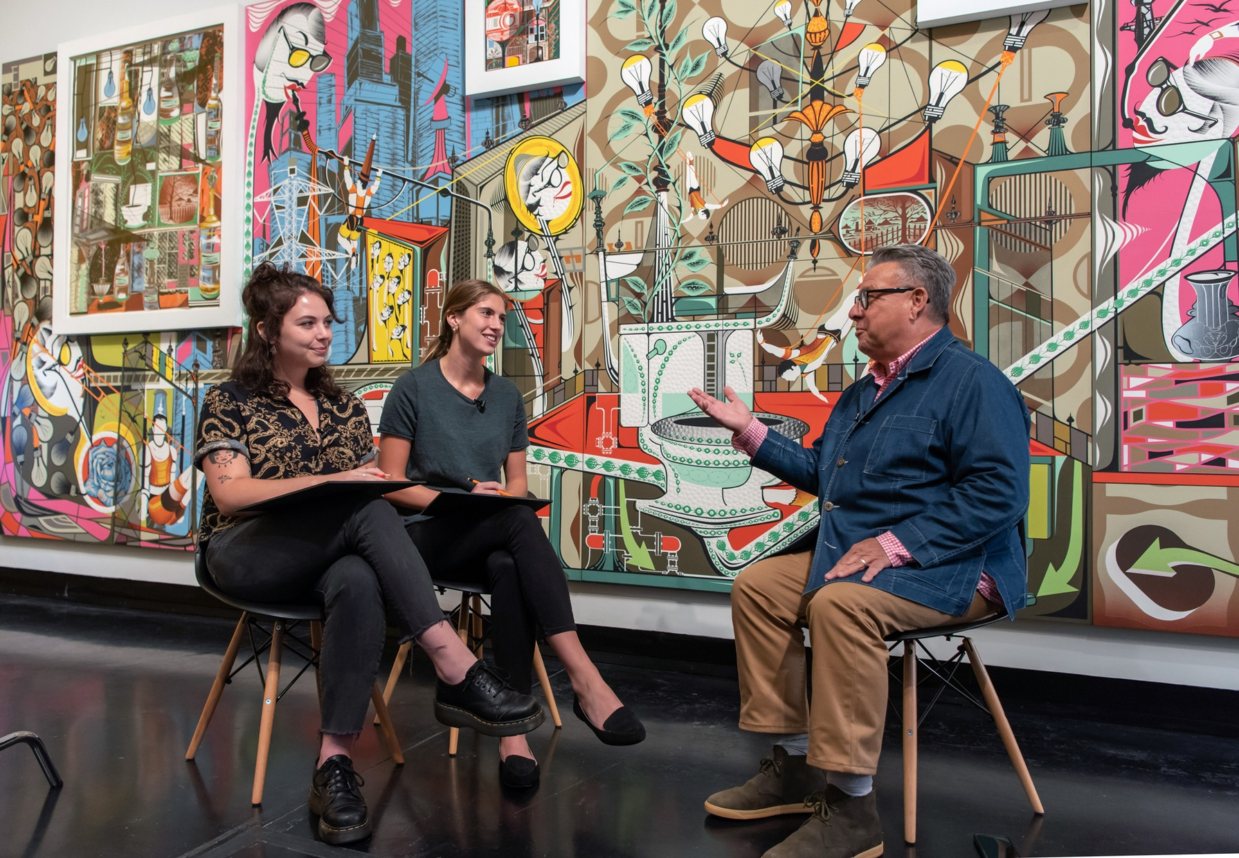 Two young, light skinned women sit in chairs across from artist Lari Pittman, a light-skinned male, also sitting in a chair. A huge and colorful painting spans the entire wall behind them.