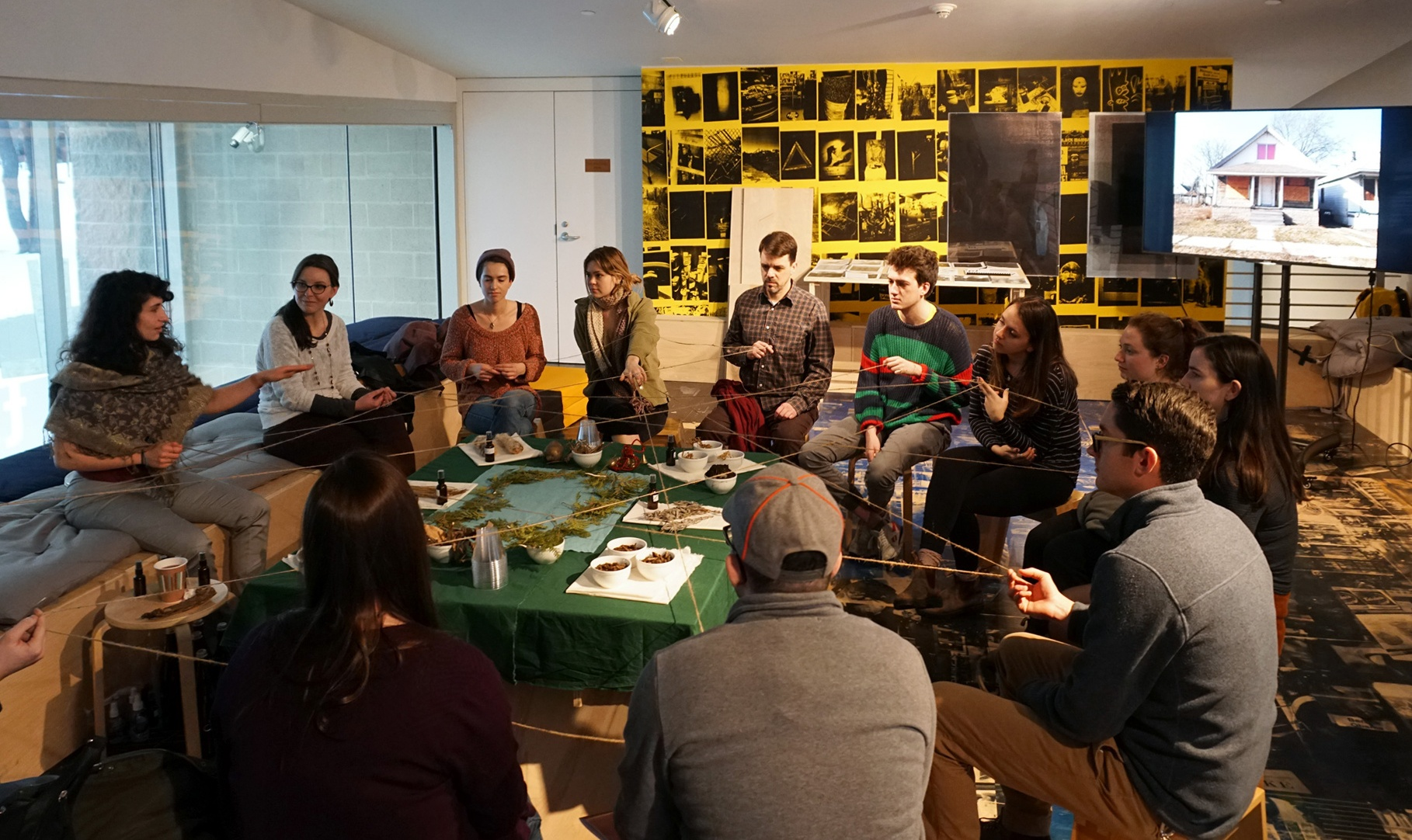 A group of people sit around a table covered with plant and earth materials holding a string that connects them all.