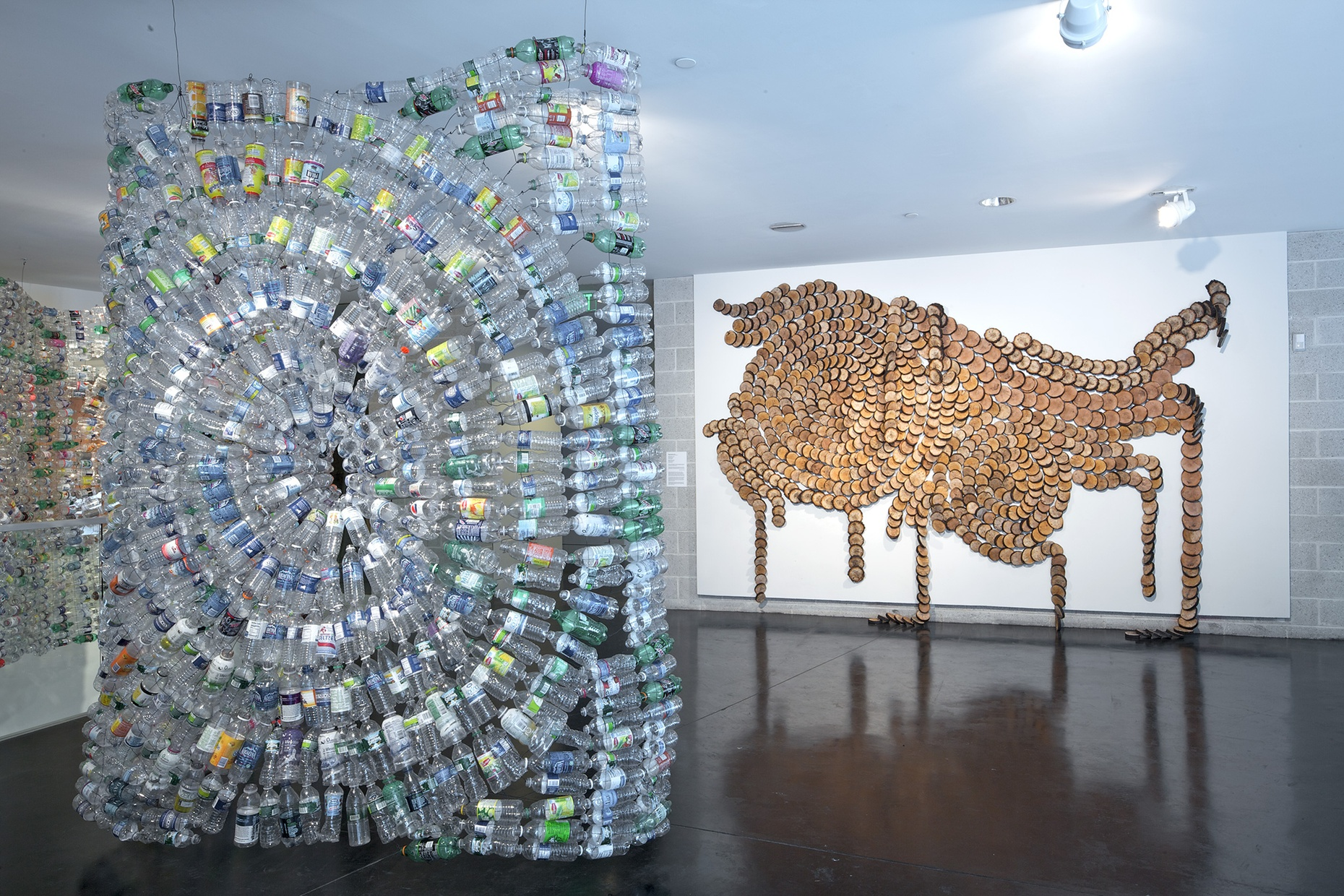 A swirly, three-dimensional sculpture made of plastic bottles in front of a white wall with an abstract design made of wooden circles.