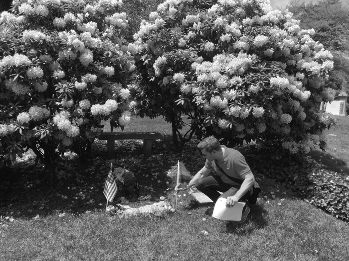FIG. 8: Ken Lustbader, codirector of the NYC LGBT Historic Sites Project, planting a rainbow flag at the Green-Wood Cemetery grave of composer/conductor Leonard Bernstein, 2018. Photograph by Amanda Davis/NYC LGBT Historic Sites Project.
