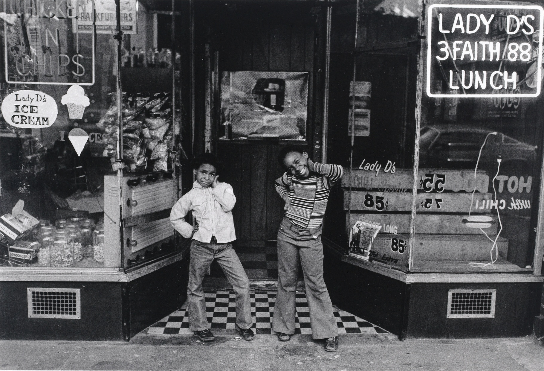 A black and white photograph of two, young, Black girls posing in front of an old ice cream store.