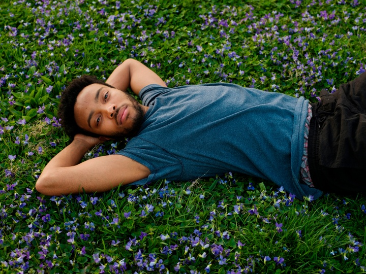 Inkjet print of a person lying in a field of green plants with small purple flowers, their arms behind their head, staring at the camera.