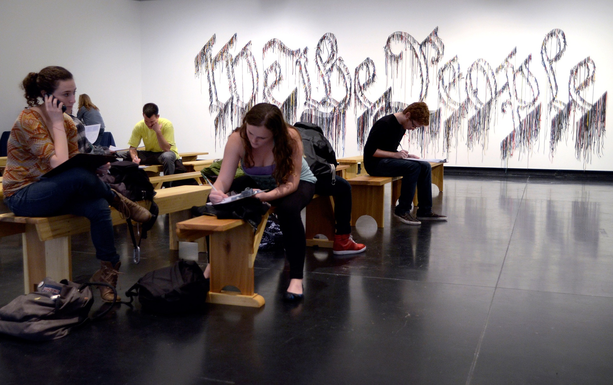 """A group of young people sit on wooden benches. On the wall behind them, """"We the People"""" is written with silver tinsel."""