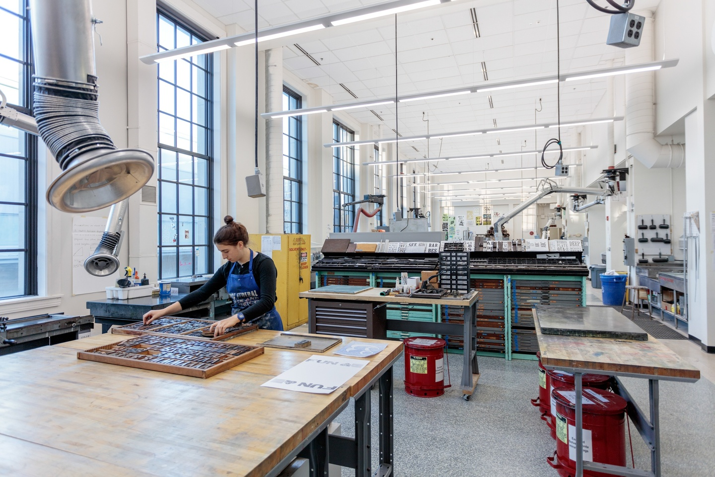 Person arranges a tray of moveable type on a table in a printmaking space with high ceilings.