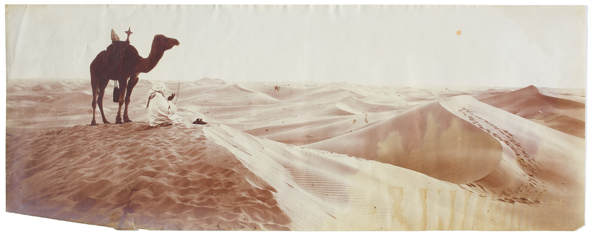 A vintage horizontal photograph of a vast desert landscape. A camel stands and a person sits atop a dune in the left foreground.