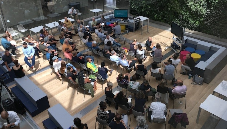 A large group of people photographed from above talk to each other in a sunny atrium.