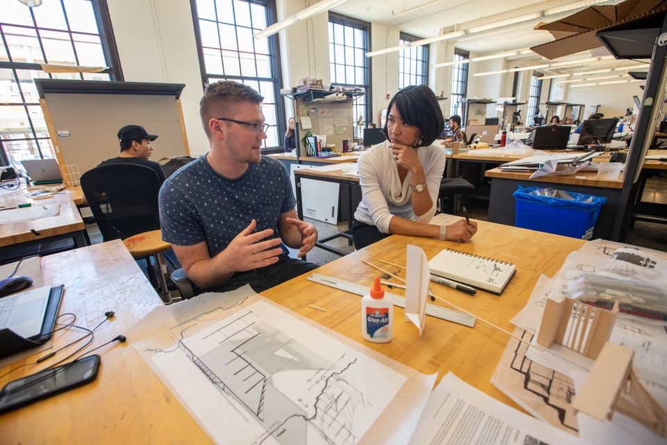 Professor consults with a student at their L-shaped desk in a large studio space filled with other private desks.
