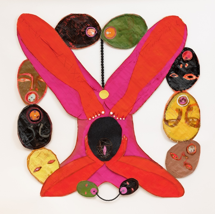 Mixed media painting featuring a vibrant, rounded pink and orange X-like figure in the center, with ovular shapes—some appearing to be heads, around the perimeter in black, olive green, yellow, and brown. Composed of ink, acrylic, freshwater pearls, lava beads, fire glass, glitter, abalone, thread, and glass beads on papyrus.