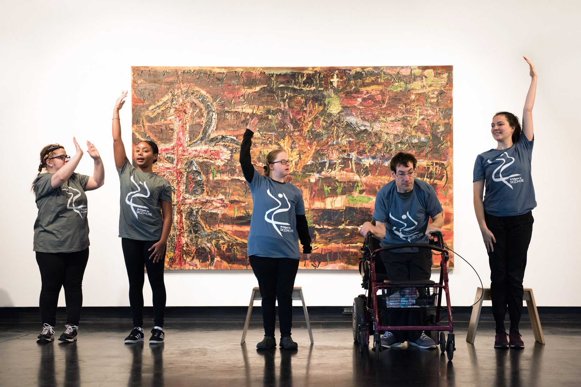 Five people pose with their arms raised in front of an abstract, earth-toned painting.