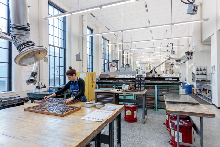 Wide angle shot of a high-ceilinged printmaking and letterpress studio.