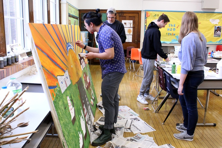 People work on a large canvas painting in an elementary school classroom.