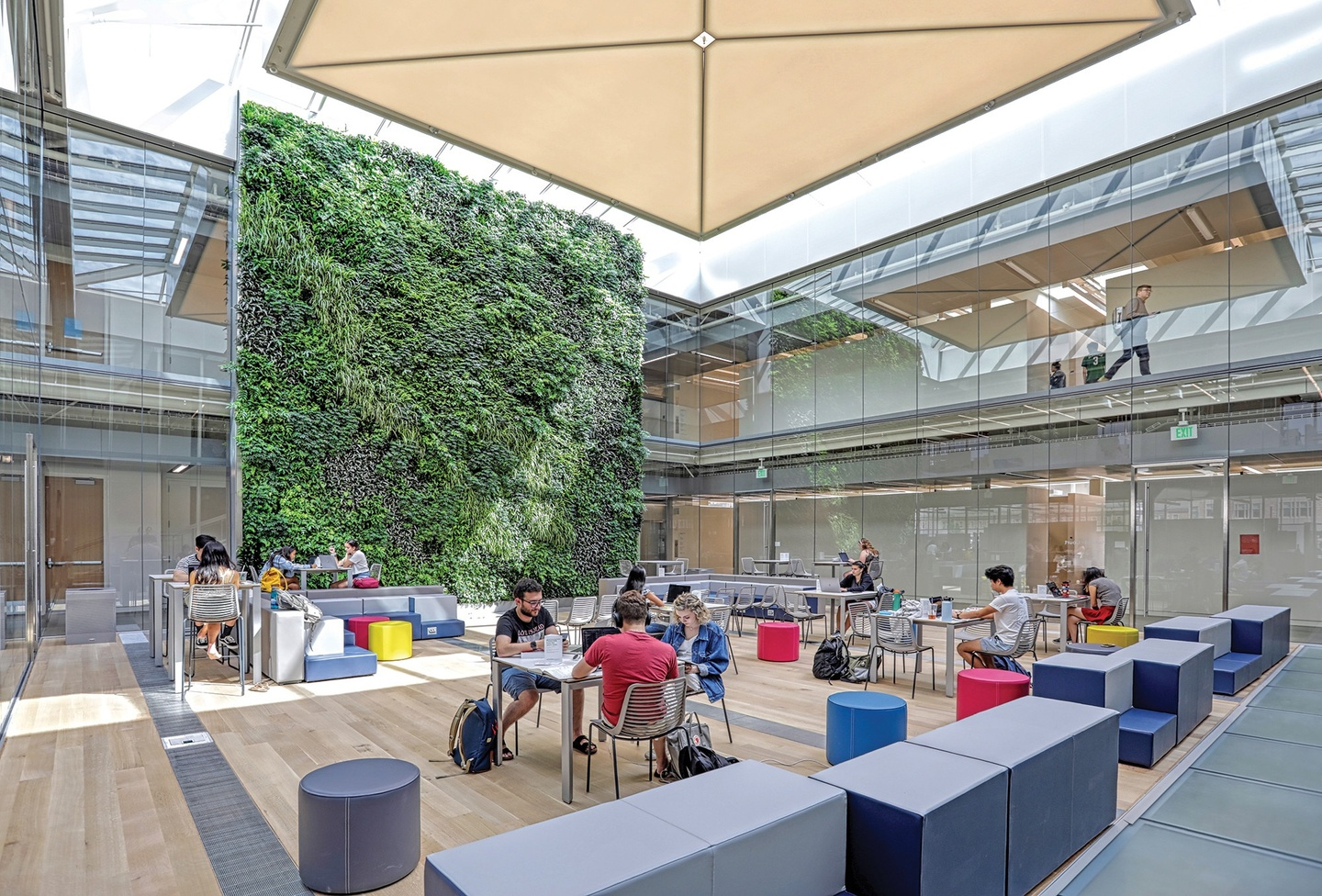 Light-filled, glass-walled court with people sitting at tables and around colorful soft seating; a two-story green wall filled with plants lines the back wall.