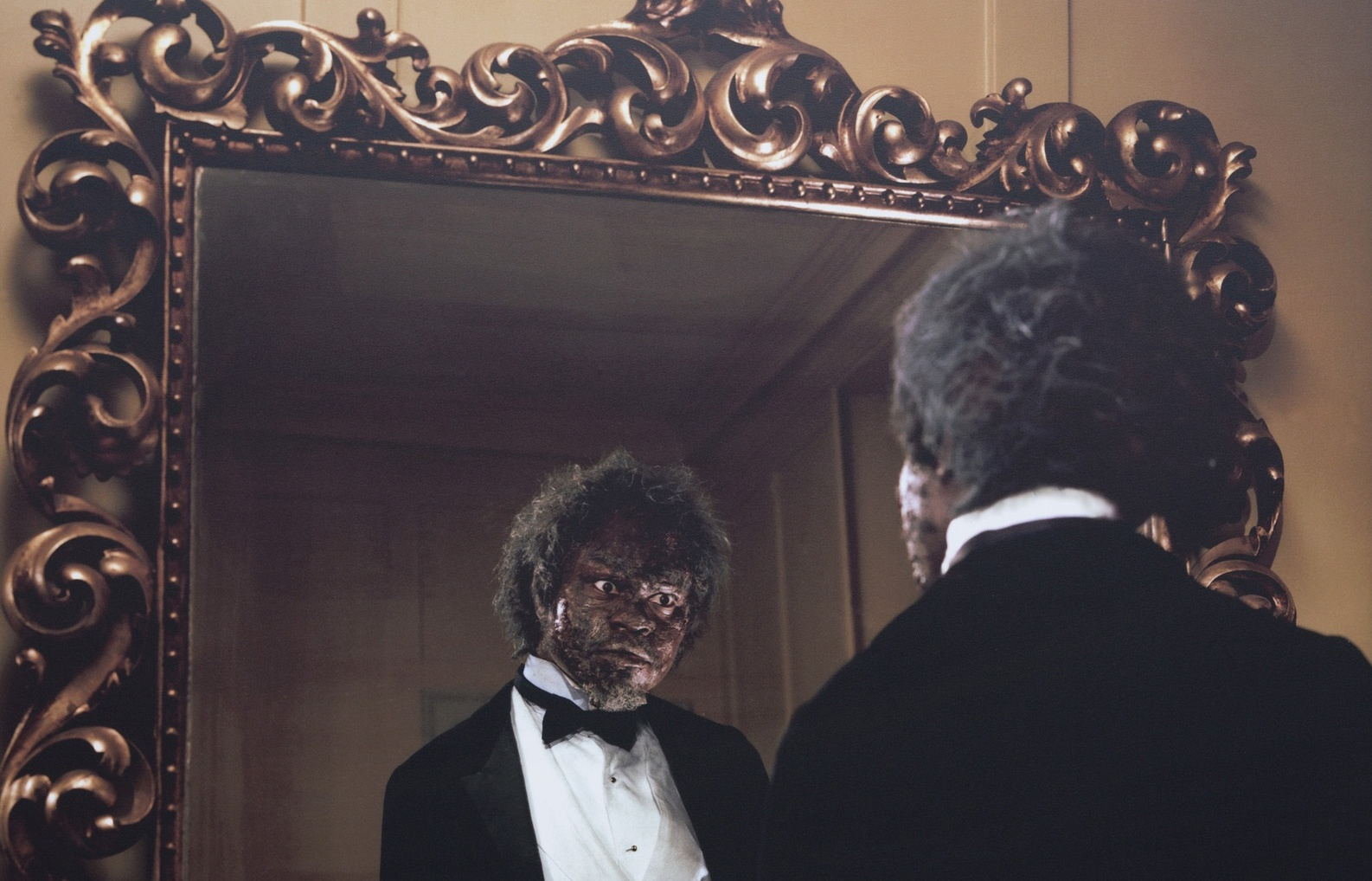 A detail of a photograph of a Black man with his back to the camera looking at his reflection in a large, decoratively framed mirror. He's wearing a black suit jacket, bowtie with a white shirt and his skin looks damaged or weathered.