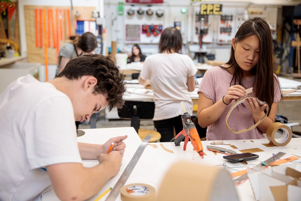 Several people sit at worktables and assemble models out of cardboard and hot glue.