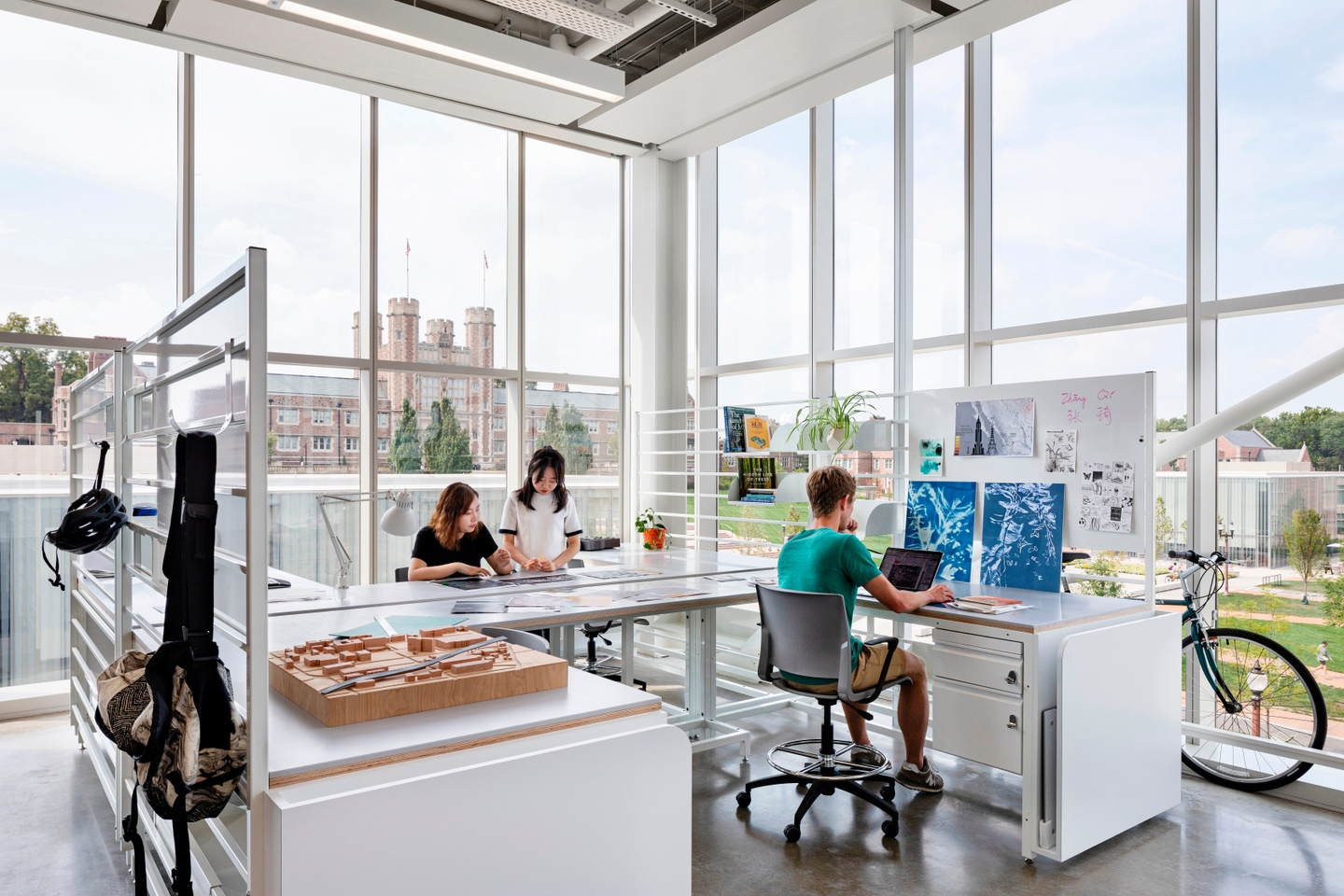 Three people work on their laptops at a modular, semi-private desk space to the backdrop of Brookings Hall, seen through the window wall.