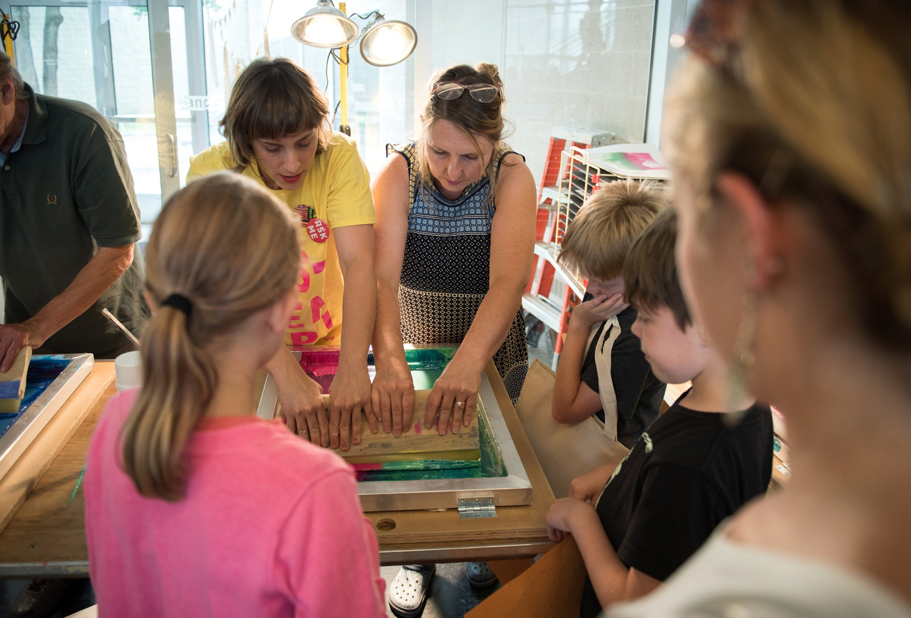 Two white women work on a screenprint while a group of children watch.