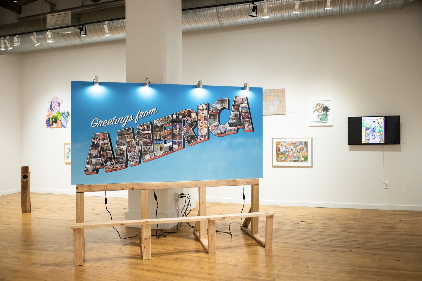 """Large, horizontally oriened vinyl sign on MDF, with a bright blue background. White script type says """"Greetings from"""" and the word AMERICA is in all caps with an outline, filled in with a variety of photos. In the background are other artworks hung on gallery walls."""