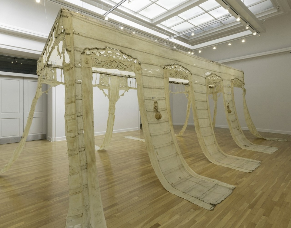 An intricate large off-white sculpture shaped like a building hanging from the ceiling in a gallery