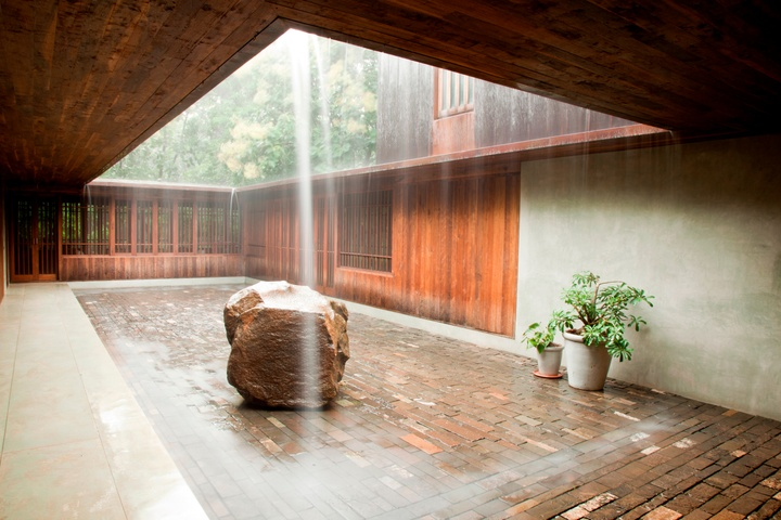 Courtyard area, with light streaming through a rectangular opening in the roof. The courtyard featured a larger, rectangular inset of brick pavers, with a larger stone boulder and a couple of green ferns. Wood walls line the back and part of the right side of the walls, and trees are visible through the roof opening.