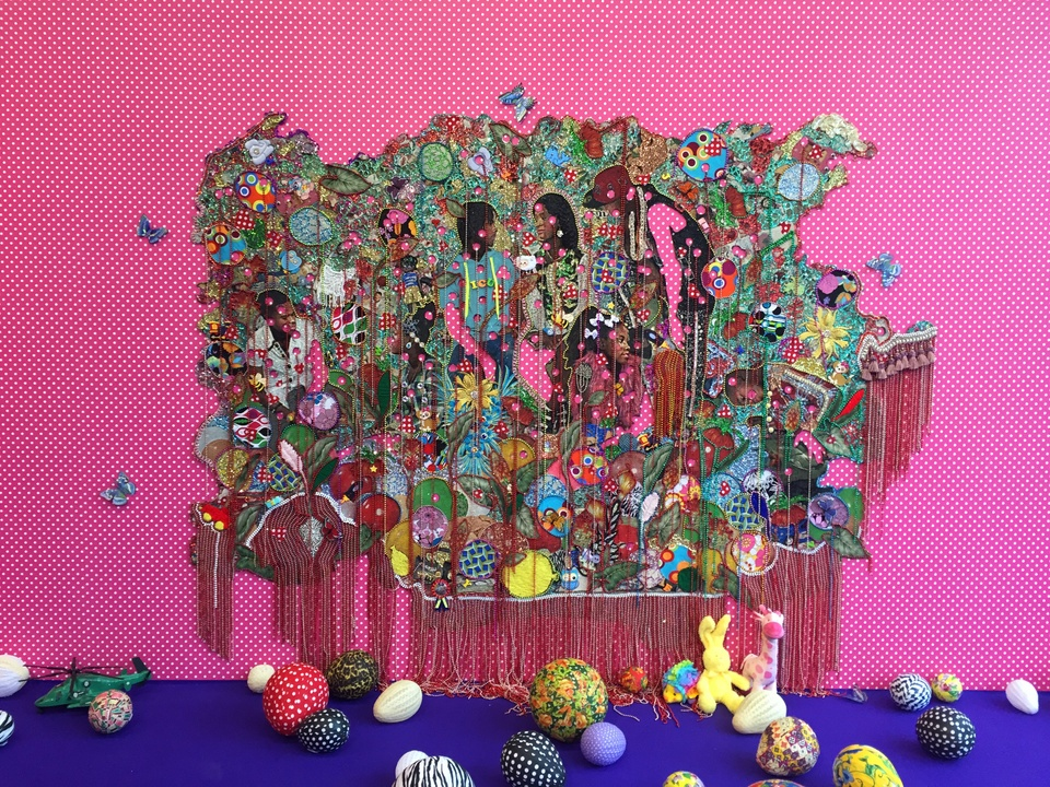 A colorful, multimedia tapestry is centered on a hot pink background with small white polka-dots, adorned with life-size butterfly sculptures. The tapestry features several Black teenagers and children casually interacting, conversing, and playing amongst oversized flowers and colorful toys and objects. Fringe and other adornments drape down over the work. The work extends from ceiling to floor. The floor is colored ultramarine and is scattered with brightly painted balls, many of which are egg-shaped, as well as stuffed animals.