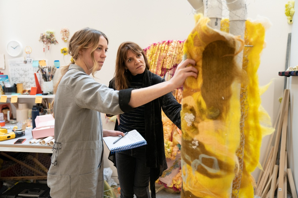Two people look at a construction of yellow felt in an artist's studio.