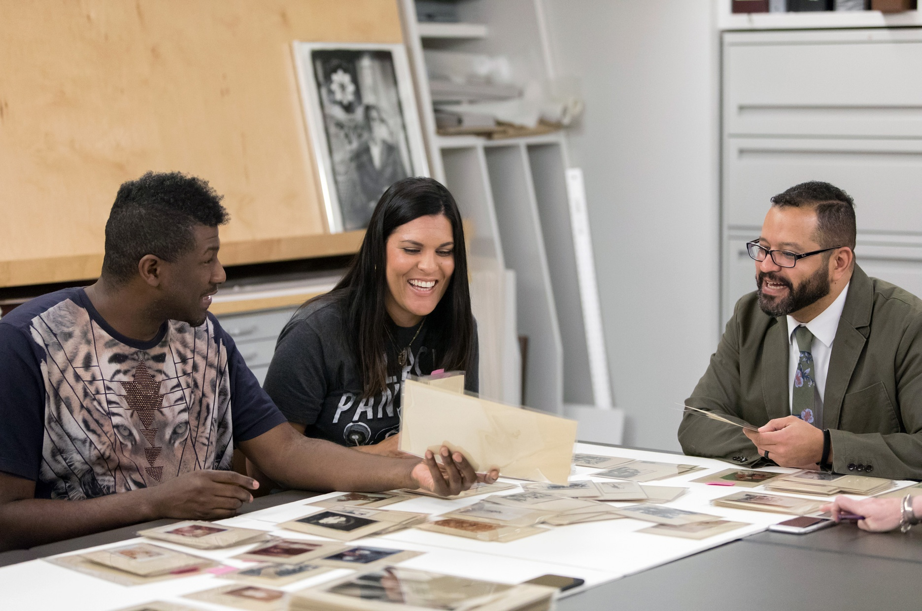 Three people sit around a table laughing and smiling looking at photographs laid out on the table.