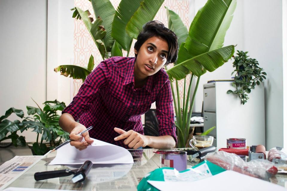 Shreyas R Krishnan working at her studio desk, a pen in hand.