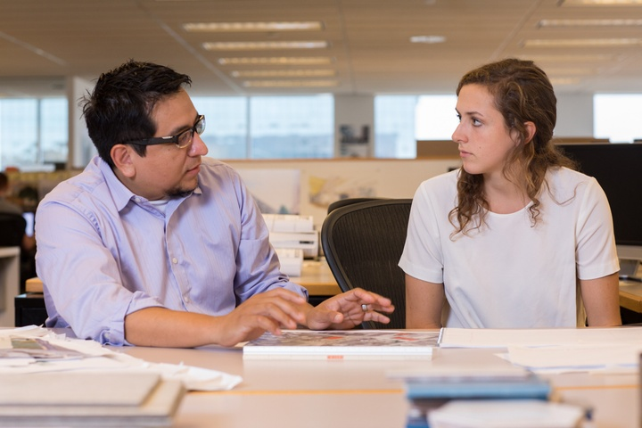 Two people sit at a table in an open office and discuss something.