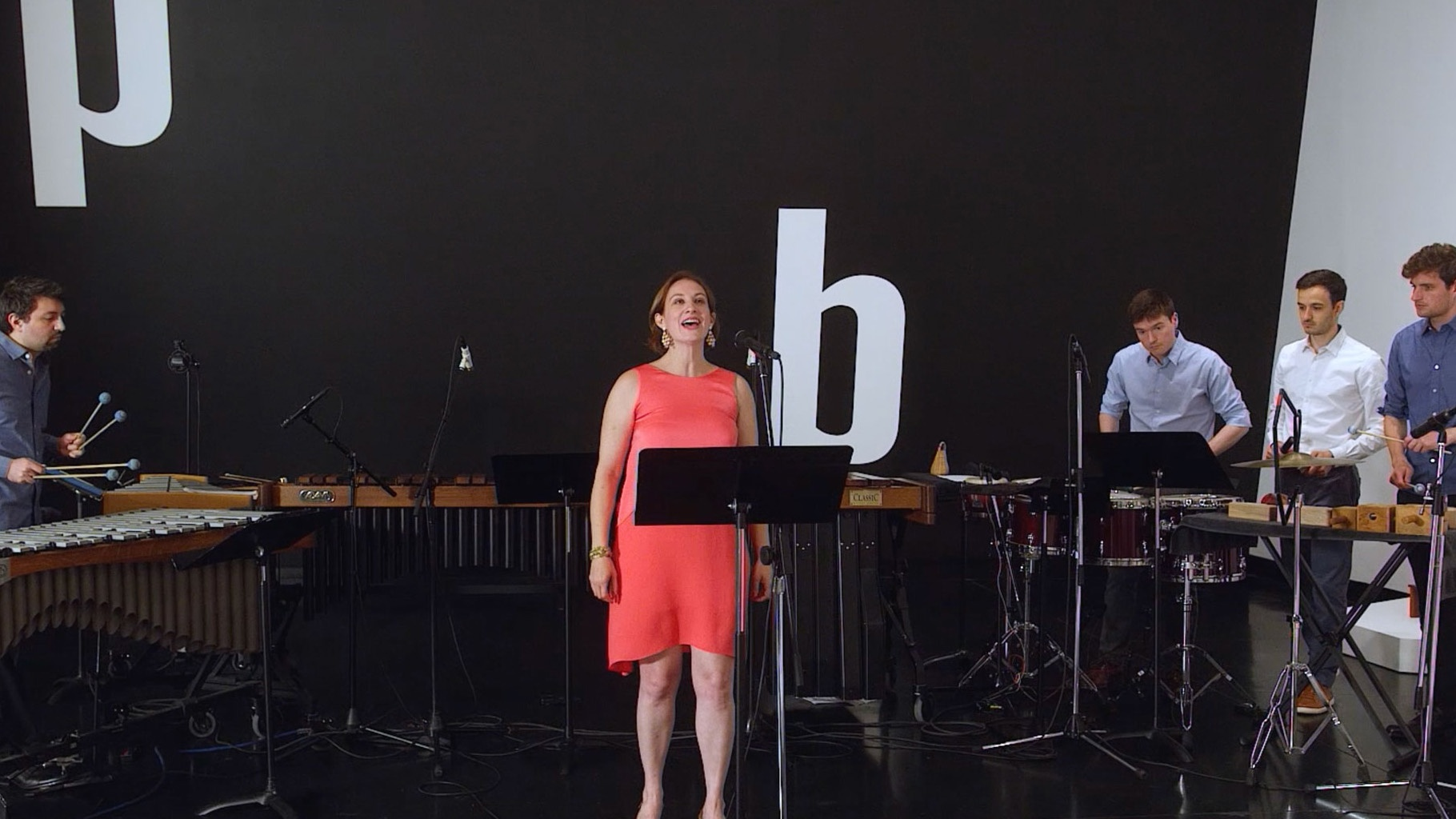 A woman sings while percussionist perform behind her